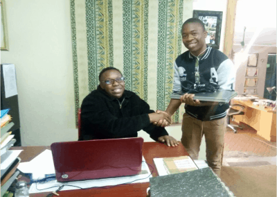 Mother Africa Trustee handing a laptop donation to one of the sponsored students